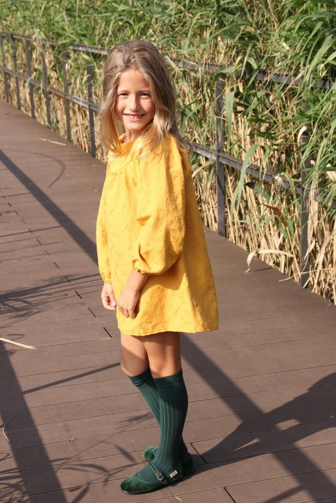vestido de niña color mostaza con manga ranglán y cuello redondo con botón verde de pasamaneria